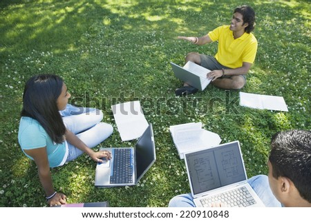 Multi-ethnic college students studying in grass - stock photo