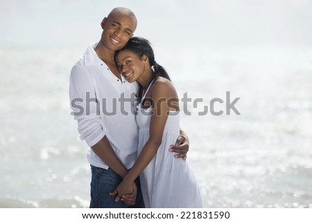 Multi-ethnic couple hugging at beach - stock photo