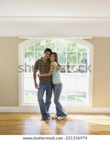 Multi-ethnic couple hugging in new house - stock photo