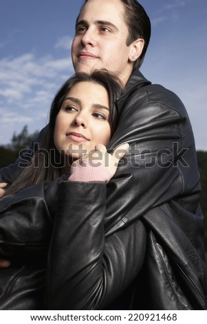 Multi-ethnic couple hugging outdoors - stock photo