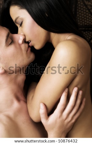 Multi-ethnic couple in passionate embrace and undressing each other during sexual foreplay