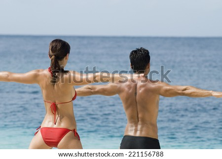 Multi-ethnic couple practicing yoga at beach - stock photo