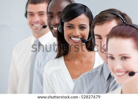 Multi-ethnic customer service representatives with headset on standing in a line - stock photo