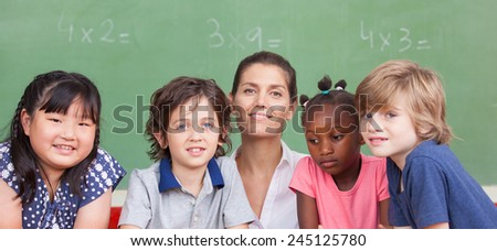 Multi ethnic elementary classroom with female teacher in front of green chalkboard. - stock photo