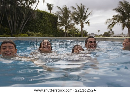 Multi-ethnic family in swimming pool - stock photo