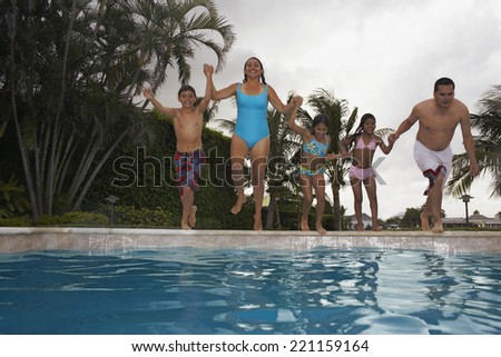 Multi-ethnic family jumping into swimming pool - stock photo