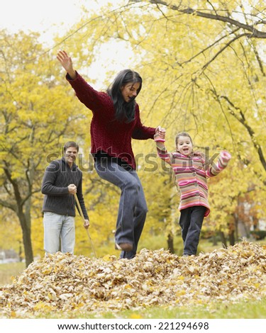 Multi-ethnic family playing in autumn leaves - stock photo