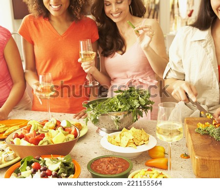 Multi-ethnic female friends preparing food - stock photo