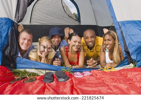 Multi-ethnic friends laying in tent - stock photo
