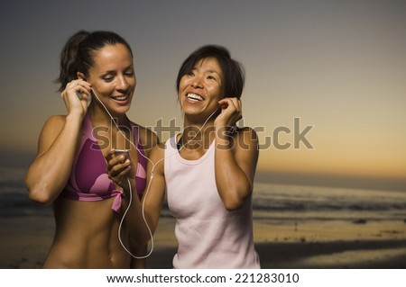 Multi-ethnic friends listening to same mp3 player - stock photo