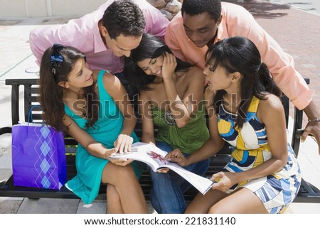 Multi-ethnic friends looking at magazine - stock photo