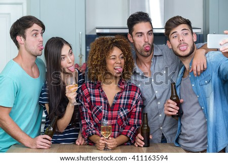 Multi-ethnic friends making faces while taking selfie by table in kitchen - stock photo