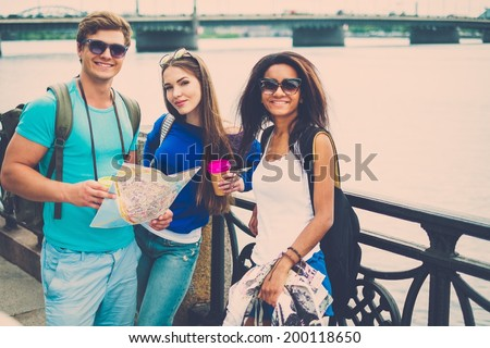 Multi-ethnic friends tourists with map and coffee cups near river in a city - stock photo