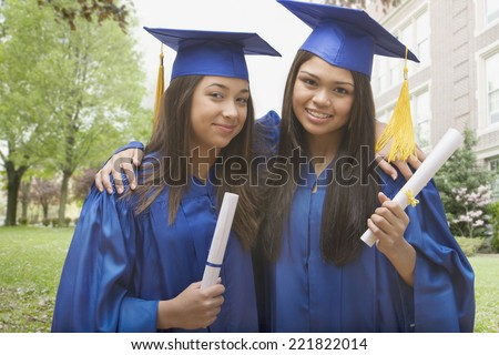 Multi-ethnic girls in caps and gowns holding diplomas and hugging - stock photo