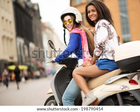 Multi ethnic girls on a scooter in european city - stock photo