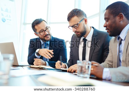 Multi-ethnic group of businessmen discussing what they learned at seminar - stock photo