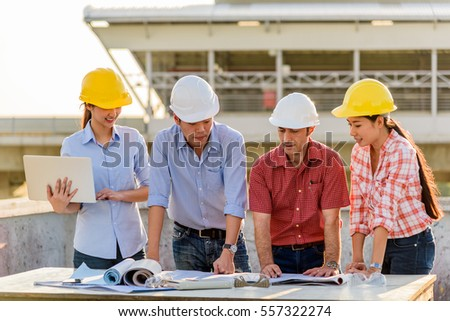 Multi-ethnic group of engineers meeting at terrace on top of construction site with evening light