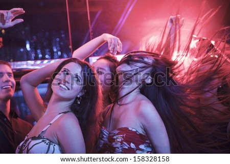Multi-ethnic group of friends dancing with hands in the air  - stock photo