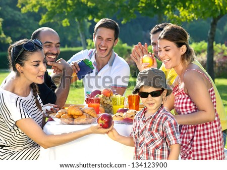 Multi ethnic group of friends enjoying a meal together outdoors in the garden with a small boy in sunglasses in the foreground - stock photo