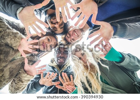 Multi-ethnic group of friends hanging out - Cheerful people meeting outdoors and having fun - People holding hands in circle formation