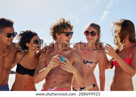 Multi-ethnic group of friends laughing after taking funny selfie with mobile phone wearing bright coloured bikinis showing sexy tanned bodies