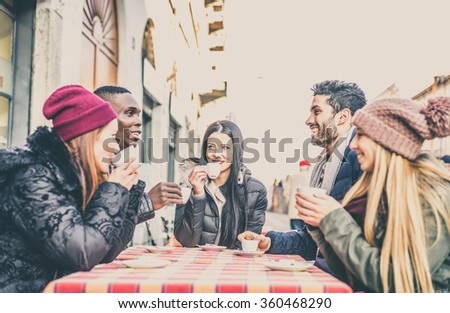 Multi-ethnic group of friends sitting in a bar and drinking coffee - Cheerful students meeting in a coffee house for a break - stock photo