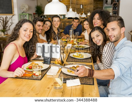 Multi-Ethnic group of happy friends lunching and making a selfie - stock photo
