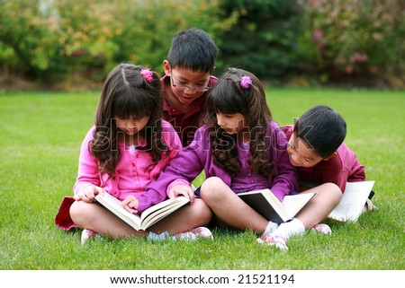 multi ethnic group of kids reading in grass