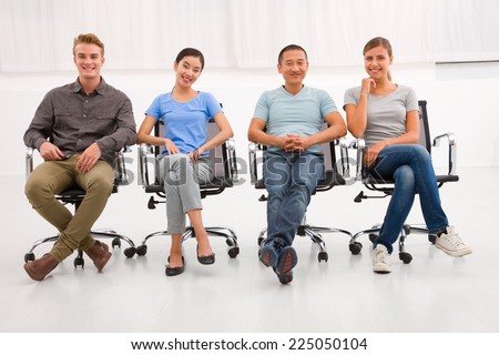 Multi ethnic group of people sitting office chair - stock photo