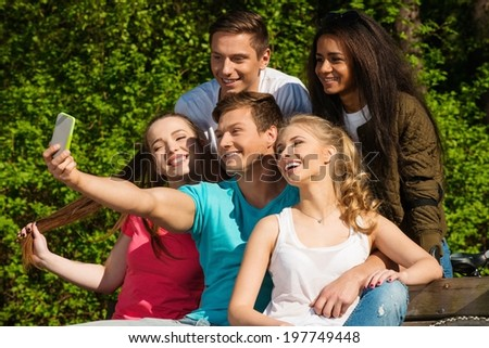 Multi ethnic group of sporty teenage friends in a park taking selfie - stock photo