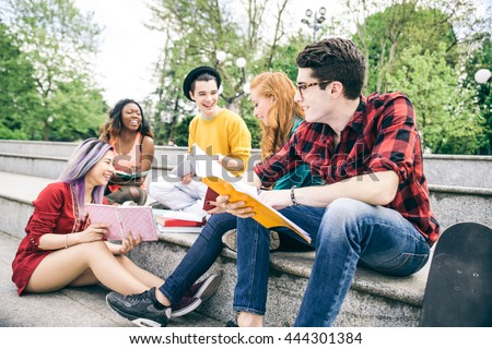 Multi-ethnic group of students studying together outdoors in a college campus - stock photo