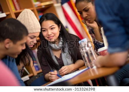 Multi ethnic group of students working on task together - stock photo