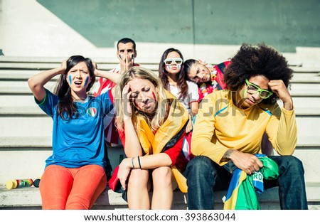 Multi-ethnic group of supporters crying for the disqualification of their teams - Unhappy and frustrated fans at the stadium - stock photo