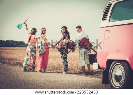 Multi-ethnic hippie friends with guitar and luggage  - stock photo
