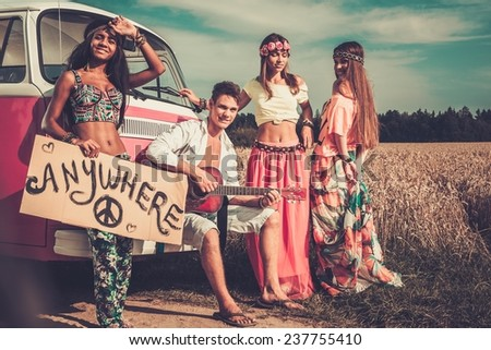 Multi-ethnic hippie hitchhikers with guitar and luggage on a road - stock photo
