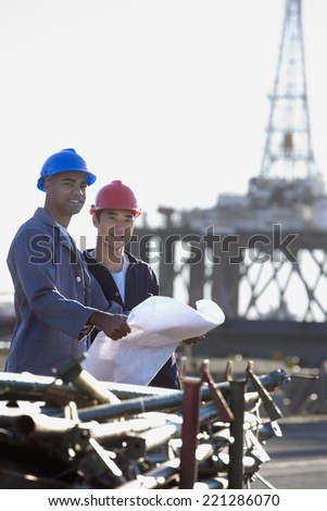 Multi-ethnic male construction workers holding blueprints - stock photo