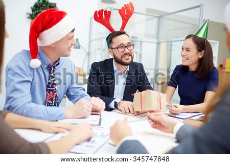 Multi-ethnic managers sitting in office and talking on Christmas day - stock photo