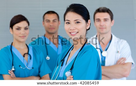 Multi-ethnic medical team smiling at the camera - stock photo