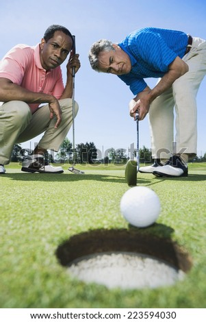 Multi-ethnic men looking at golf ball - stock photo