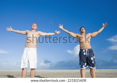 Multi-ethnic men with arms outstretched - stock photo