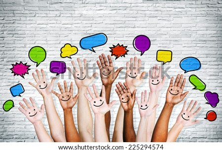 Multi ethnic people's hands raised with speech bubble by brick wall. - stock photo