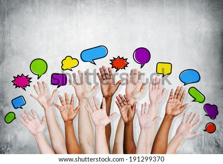 Multi ethnic people's hands raised with speech bubbleb by concrete wall. - stock photo