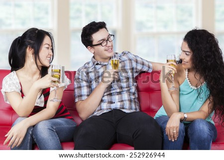 Multi ethnic people sitting on sofa while drinking champagne and talking each other - stock photo
