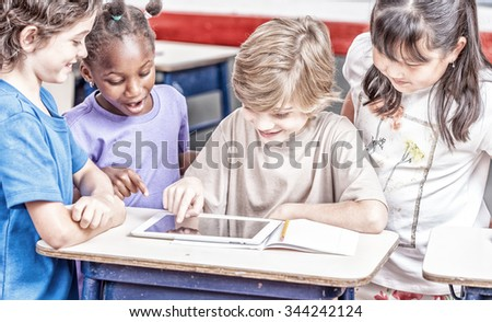 Multi ethnic primary classroom. Schoolchildren playing with tablet. - stock photo