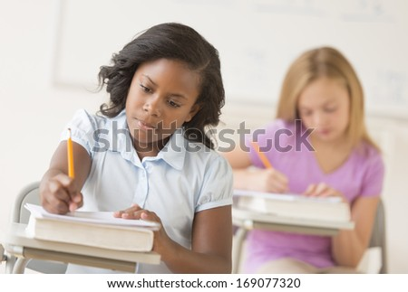 Multi-ethnic school children writing notes at desk in classroom - stock photo