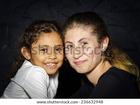 Multi-ethnic sisters face-to-face studio portrait on dark background - stock photo