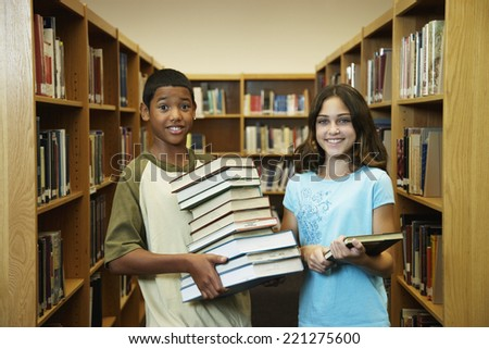 Multi-ethnic students holding library books - stock photo