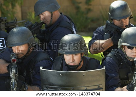 Multi ethnic swat officers aiming with gun behind shield
