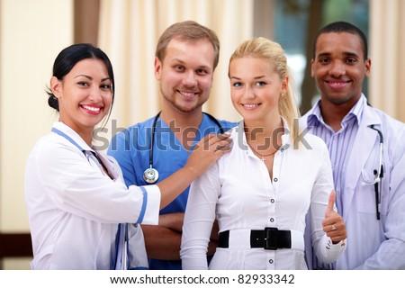 Multi-ethnic team of confident happy doctors with their happy patient - stock photo