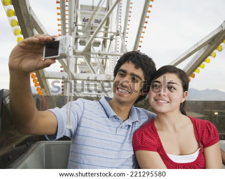 Multi-ethnic teenaged couple on carnival ride - stock photo